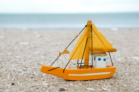 gloaming: old colorful wooden boat figure on the beach in the evening Stock Photo