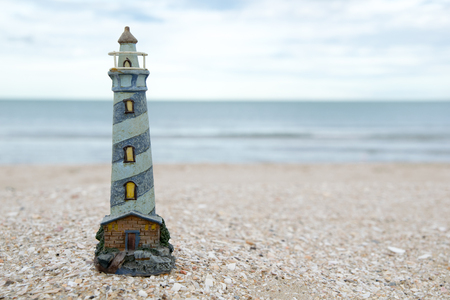 gloaming: cute lighthouse figure on the beach in the evening