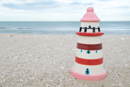 likable: cute colorful lighthouse ceramic doll on beach