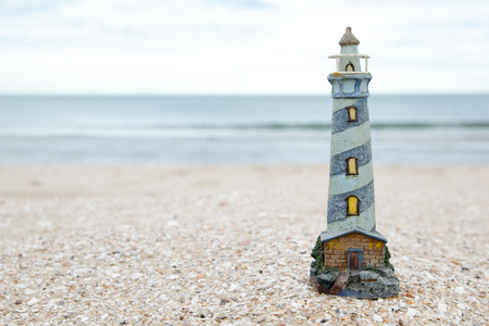 engaging: cute lighthouse figure on the beach in the evening