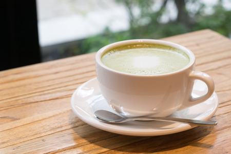 potation: Close up hot green tea in a cup on wooden table Stock Photo