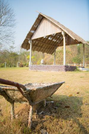 pavillion: old steel wheel barrow with wooden pavillion background