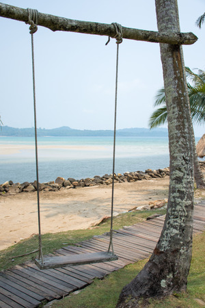 stale: Old wooden swing on the beach