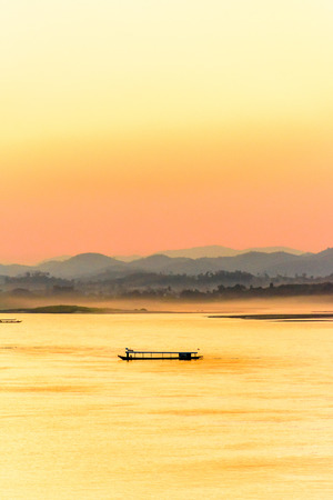 Passenger ship on the Mekong river in the evening with fog and mountains background.