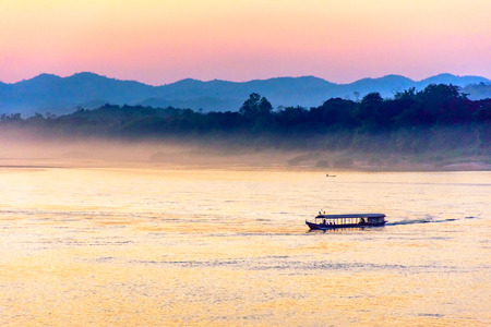 cloud drift: Passenger ship on the Mekong river in the evening with fog and mountains background.