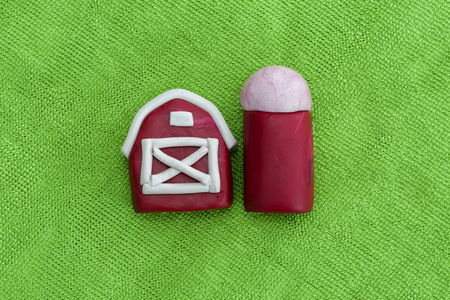 Plasticine red barn on colorful background