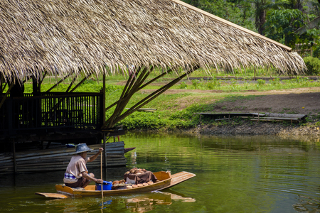 A man is boating to bring his goods to sell at floating market.