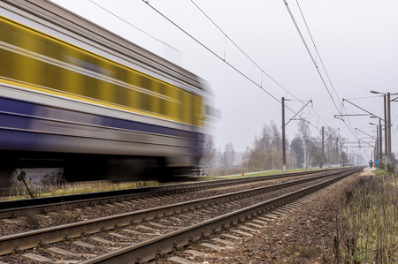 remoteness: Electric passenger train traveling on the railroad tracks. Remoteness visible to passengers who will train.