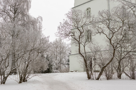 without windows: Church Park in winter, snowing. Snow-covered trees. Stock Photo