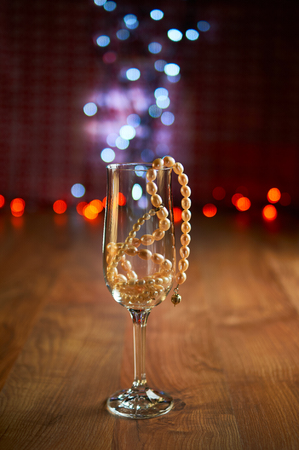 uncork: Glass of champagne with pearl beads and bokeh. Selective focus