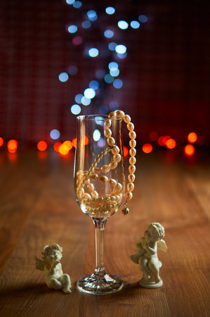 jahreswechsel: Glass of champagne with pearl beads and bokeh. Selective focus
