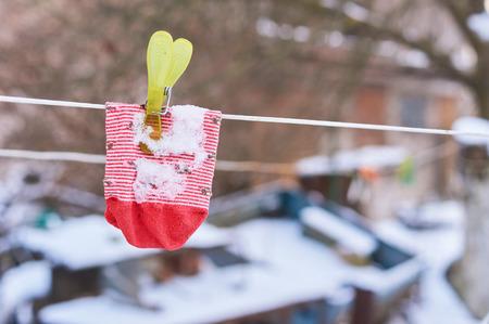 ahorcada: El calcetín de rayas para niños se cuelga en un alambre con una clavija en invierno. día frío, línea de lavado en el jardín Foto de archivo