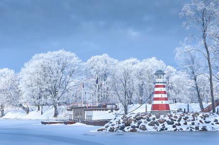 Navigatie Vuurtoren bevroren water kust berijpte bomen rijp sneeuw steiger pier toeristische schip zonnige dag Stockfoto - 70856902