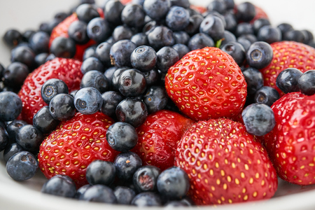 Assorted blueberries and strawberries in a white dish, sleek focus, different angles, close-up Stock Photo