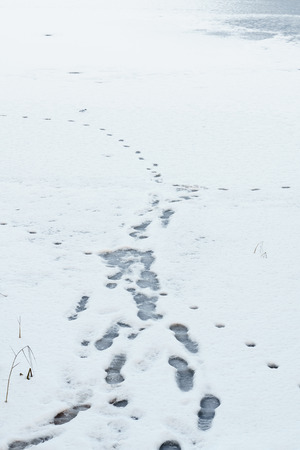 foot footprints in snow, snow structure, snow-covered and frozen puddles, trail on the ice 스톡 콘텐츠