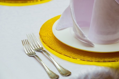 Two forks lying at yellow plates