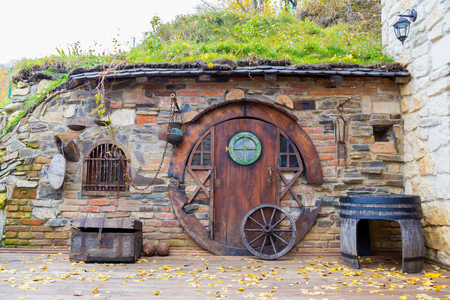 fench: The house of hobbits. The old house near which a barrel and a chest. Ukraine, Lviv hotel complex Cavalier 10.10.2017 Editorial