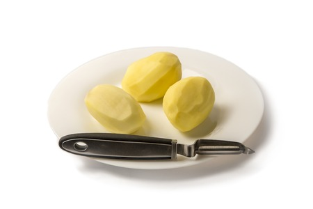 Three potatoes on a plate isolate