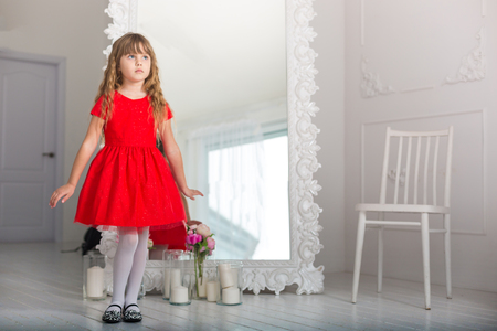 little girl in a red dress wistful glance at the mirror