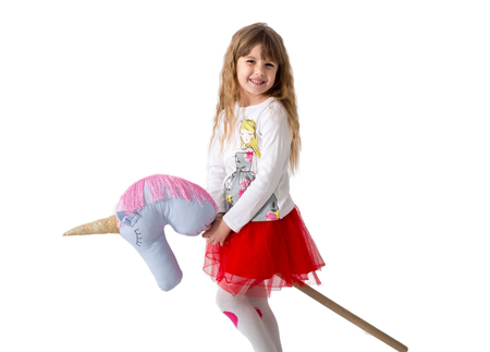 kleines Mädchen hält einen Spielzeugrücken zwischen den Beinen auf einem weißen Hintergrund. Isoliert