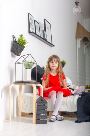 bed skirt: little girl in a red dress sitting on the bed and looks at the camera Stock Photo