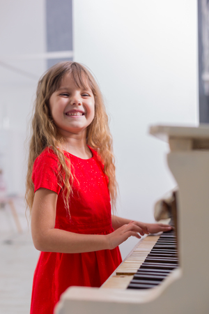 Young girl in a red dress plays the piano