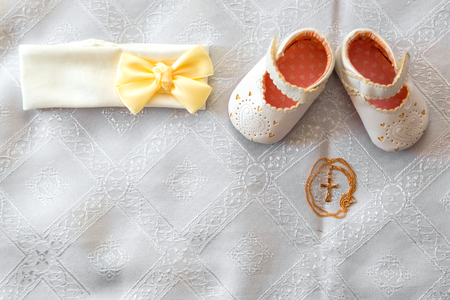 Christening details. On white baby shoes and bandage. Golden cross on a white canvas