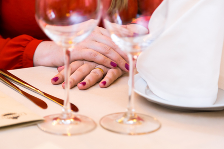 Durk in red is waiting at the restaurant. Table set service with silverware and glass stemware at restaurant before. Stock Photo