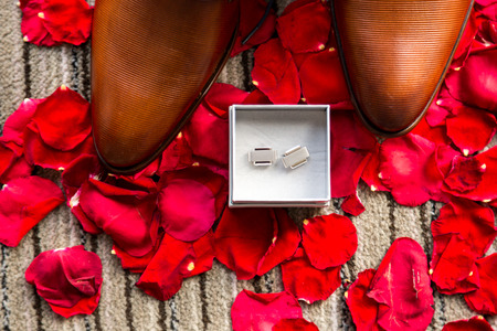 Wedding mans accessories on red rose petals