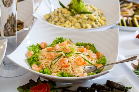 Pasta with shrimps in a white plate on a banquet table