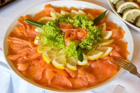 rape: Pieces of salmon are decorated with lemon on a white plate of the buffet table Foto de archivo