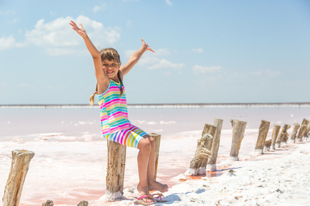 Little girl on the background of salt lakes of the dead sea and pink rose, raised her hands up