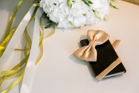 Accessories grooms wedding day. Mobile phone and butterfly