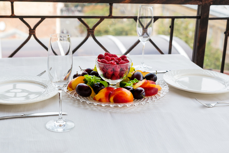 Plate of fruit with raspberries, grapes and plums is on the table for two