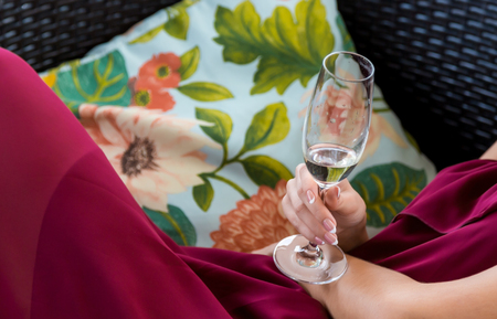 A glass of champagne in the hand of a young girl Stock Photo
