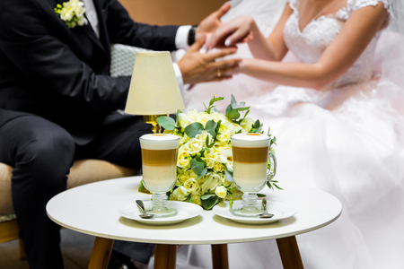 Hands of the bride and groom for a cup of coffee. Wedding bouquet on the table. Stock Photo