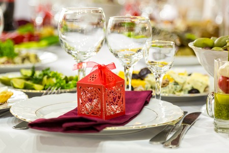 Banquet table, there is a red box with a gift on the plate.