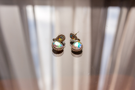 Earrings with diamonds macros are lying on the glass and shine in the sun in different colors.