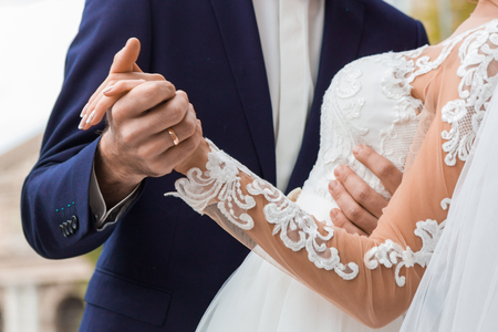The bridegroom holds the brides hand, the moment of the dance. Zdjęcie Seryjne