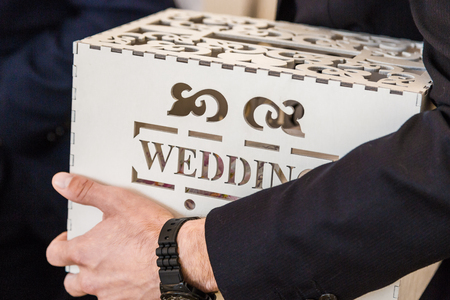 Man holds in his hand a wedding box with a wedding inscription for wedding greetings and gifts.