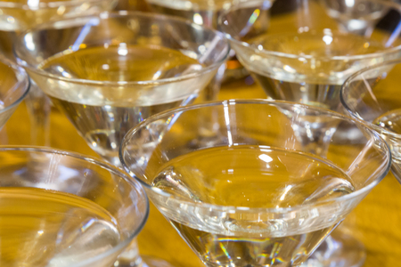 Several glasses of the famous Martini cocktail stand on a bar table