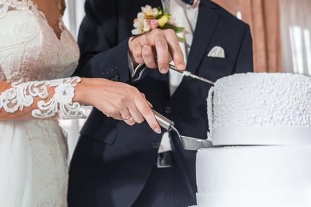 Brides cut a wedding cake holding a slice