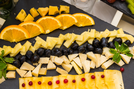 Authentic buffet, assorted fresh fruits, berries and citrus fruits. Morning atmospheric lighting, fashionable trendy spot soft focus. Preparation for design creative menu. Zdjęcie Seryjne