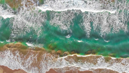 Aerial view of the waves coming to the shore. Background or text