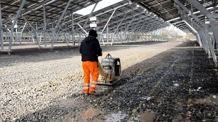 An employee using a vibrating machine compresses the rubble on the future Parking lot under the solar panels