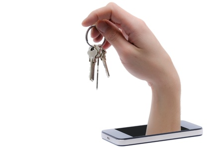 mobile security: A hand comes out a smartphone and steals a bunch of keys Stock Photo