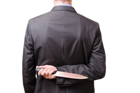 disloyal: A young businessman holding a butcher knife behing his back