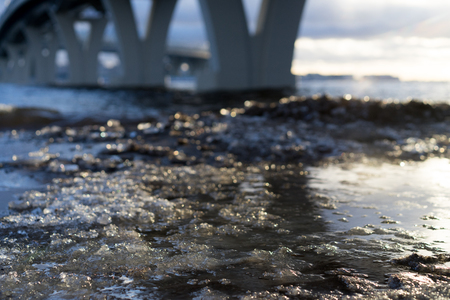 Close up picture of beachs surface. Ice is melted. Some concrete constructions are on a background. Sky is covered by clouds. Some sun lights reflects on melted surface of ice cover. Waves comes. Stok Fotoğraf