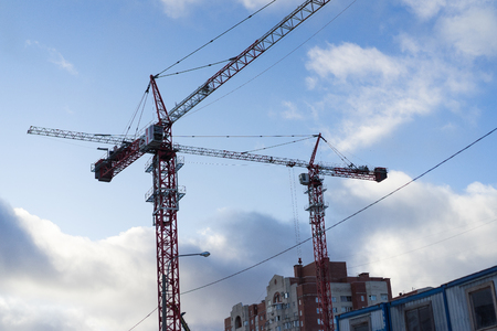 Tall red color metal tower cranes are working. Column cranes have high height. Blue sky woth white clouds are on a background.