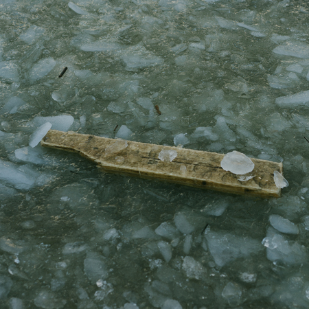 Old timber desk is clutched between ice. Picture is in dark depressive colors. Water is frozen around a wood board. Weather is cold winter. Stok Fotoğraf